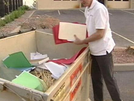 A man retrieving sensitive documents from within a dumpster