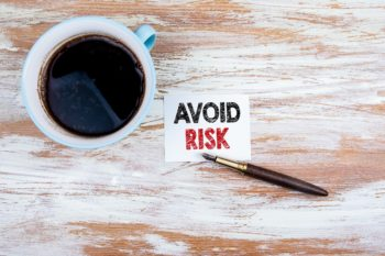 Avoid Risk concept. Paper letter and pen on a wooden table