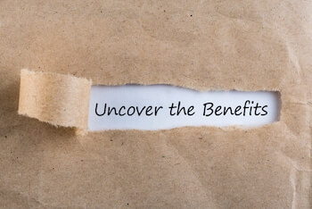 Uncover The Benefits text on brown envelope. Word Uncover The Benefits on torn paper.