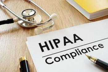 HIPAA Compliance application and stethoscope on a desk.